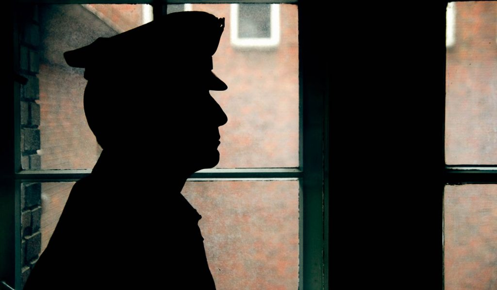 image of silhouetted police officer in dark hallway