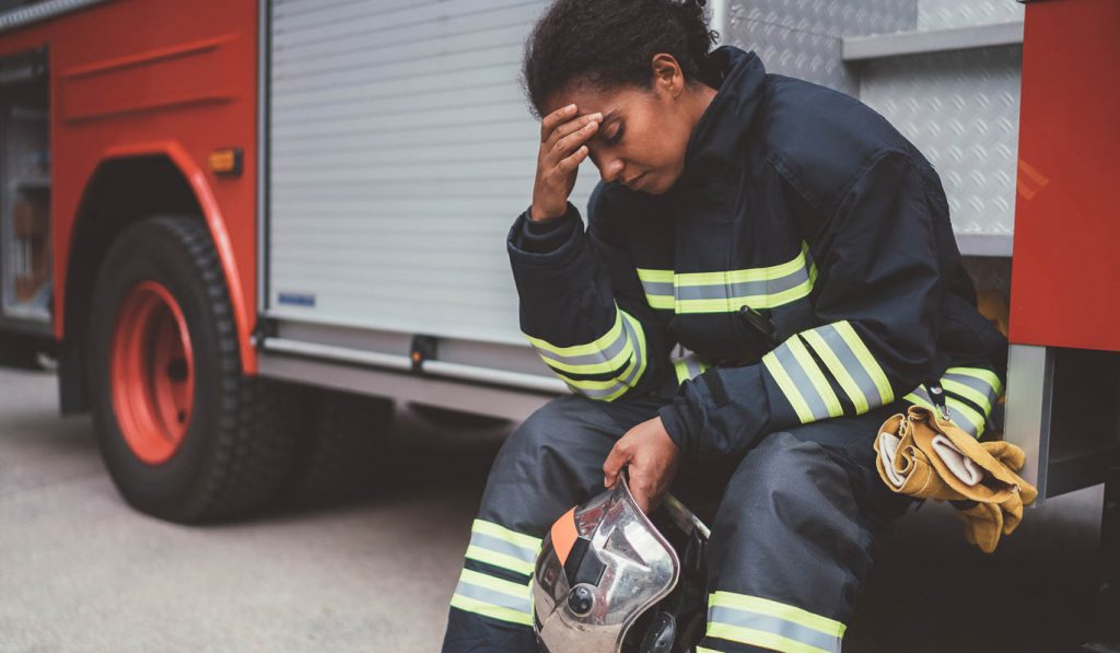 image of firefighter sitting on firetruck, hand to forehead